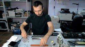 O trabalhador meados de do tiro repara o material eletrônico video estoque