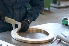 O trabalhador mede o detalhe, um anel metálico brilhante com um compasso de calibre em uma tabela verde de trabalho na fábrica, a imagem de stock