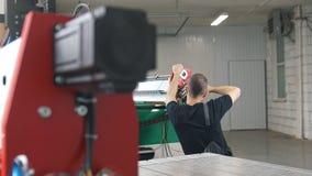 O trabalhador monta máquinas industriais do CNC na fabricação filme