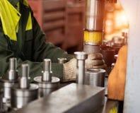 O trabalhador monta a pressão do rolamento em um grampo do metal na máquina, monta a unidade terminada, close-up, funcionamento imagens de stock royalty free