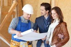 O trabalhador mostra planos de desenvolvimento da casa foto de stock