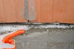 O trabalhador mostra o salitre na fundação, umidade capilar imagens de stock