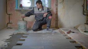 O trabalhador nas verificações de formulário da construção o nível da superfície no azulejo, põe então o cimento sobre o assoalho filme