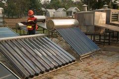 O trabalhador nas verificações do uniforme e do capacete que concentram energias solares com plano Plat o coletor do coletor e do imagem de stock