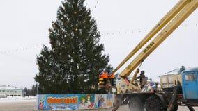 O trabalhador no berço do manipulador decora a árvore de Natal filme