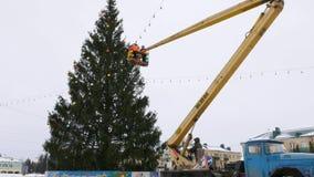 O trabalhador no berço do manipulador decora a árvore de Natal video estoque