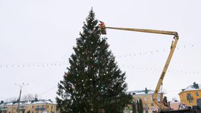 O trabalhador no berço do manipulador decora a árvore de Natal vídeos de arquivo