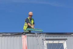 O trabalhador no canteiro de obras limpa o telhado fotos de stock royalty free