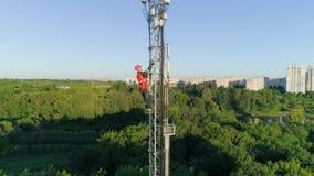 O trabalhador no capacete de segurança escala altamente na torre de rádio da telecomunicação na paisagem bonita da cidade do fund video estoque
