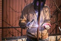 O trabalhador no metal de soldas da máscara protetora com uma máquina de solda fotografia de stock royalty free