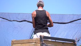 O trabalhador no pomar de maçã está instalando a anti rede da saraiva acima das árvores filme