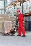 O trabalhador no trabalho com mão pôr o jaque da pálete Imagem de Stock