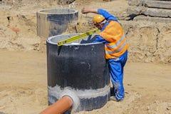 O trabalhador no uniforme alaranjado no canteiro de obras mede a profundidade do concreto bem fotografia de stock royalty free