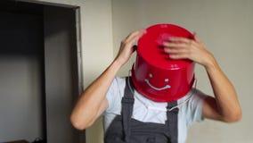 O trabalhador no uniforme com a cubeta vermelha em sua cabeça tem o divertimento e a dança vídeos de arquivo