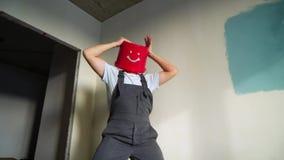 O trabalhador no uniforme com a cubeta vermelha em sua cabeça tem o divertimento e a dança video estoque