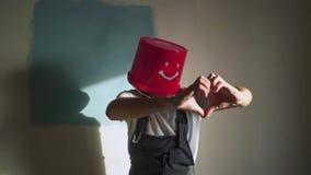 O trabalhador no uniforme com a cubeta vermelha em sua cabeça tem o divertimento e a dança filme
