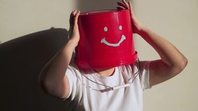 O trabalhador no uniforme com a cubeta vermelha em sua cabeça tem o divertimento video estoque