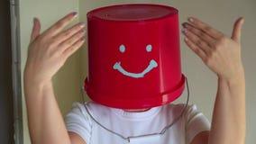 O trabalhador no uniforme com a cubeta vermelha em sua cabeça tem o divertimento filme