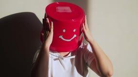 O trabalhador no uniforme com a cubeta vermelha em sua cabeça tem o divertimento vídeos de arquivo