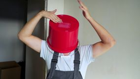 O trabalhador no unifrom com a cubeta vermelha em sua cabeça tem o divertimento e a dança filme