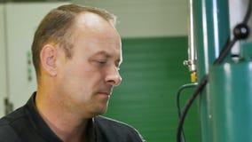 O trabalhador no Workwear gerencie ao redor a alavanca nas tubulações de gás filme