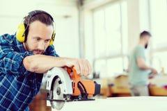 O trabalhador novo em uma oficina dos carpinteiros com mão viu foto de stock