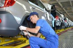 O trabalhador novo no transporte de conjunto da planta do automóvel Fotografia de Stock
