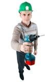 O trabalhador novo prende uma broca em sua mão Imagens de Stock