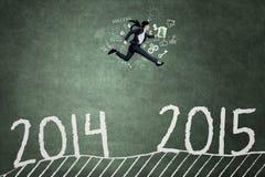 O trabalhador novo pula com o número 2014 2015 Foto de Stock
