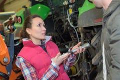O trabalhador novo verifica o motor de trator da pressão imagens de stock