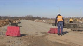 O trabalhador obstrui uma entrada especial do bloco na estrada que está sob a construção, industrial filme