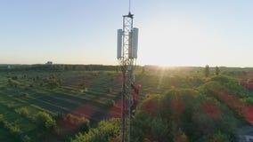 O trabalhador obtém para baixo da torre de rádio da telecomunicação com a ajuda de amarra no fundo da paisagem bonita filme