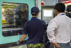 O trabalhador opera a máquina da imprensa da modelação por injeção foto de stock