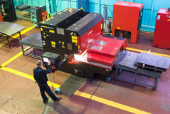 O trabalhador opera a máquina metalúrgica automatizada Fotografia de Stock Royalty Free