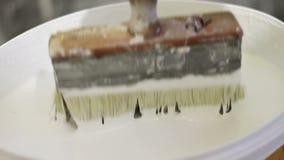O trabalhador põe a escova em uma cubeta da pintura branca filme