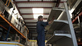 O trabalhador põe a prateleira sobre o suporte Fotos de Stock