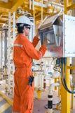 O trabalhador a pouca distância do mar da plataforma petrolífera, operador da produção opera a válvula usando o painel do tela tá fotos de stock royalty free