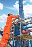 O trabalhador a pouca distância do mar da plataforma petrolífera prepara a ferramenta e o equipamento para gáss da perfuração bem foto de stock
