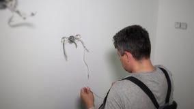 O trabalhador prepara fios para conectar quadros da roseta do soquete em furos da parede da gipsita video estoque
