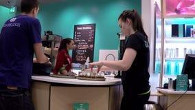 O trabalhador prepara o chá da amostra para o cliente dentro do shopping de Burnaby filme