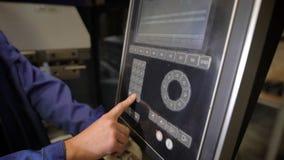 O trabalhador pressiona botões do painel da máquina-instrumento com controle programado numérico O coordenador configura a video estoque