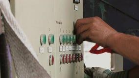 O trabalhador pressiona os botões vermelhos e verdes na fábrica filme
