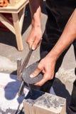 O trabalhador produz a ardósia para telhas usando um martelo da ardósia Fotos de Stock