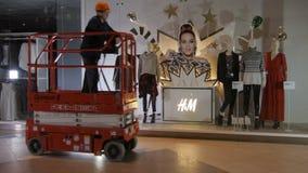 O trabalhador qualificado conduz o transportador vermelho contra a janela da loja filme