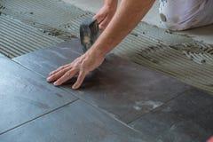 O trabalhador que coloca telhas de assoalho cerâmicas no esparadrapo surge imagens de stock