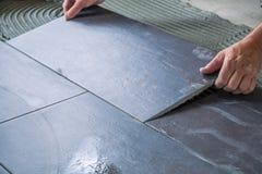 O trabalhador que coloca telhas de assoalho cerâmicas no esparadrapo surge fotografia de stock