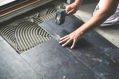 O trabalhador que coloca telhas de assoalho cerâmicas no esparadrapo surge fotos de stock