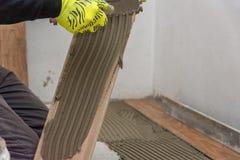 O trabalhador que coloca telhas de assoalho cerâmicas no esparadrapo surge foto de stock