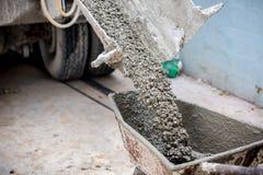 O trabalhador que guarda o trole para o apoio que derrama crete misturou o caminhão do moedor do almofariz do cimento foto de stock
