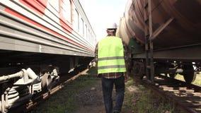 O trabalhador Railway vai ao longo do trem com uma verificação vídeos de arquivo